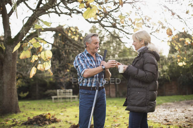 Пожилые пары кавказской с грабли, пить кофе в саду — стоковое фото