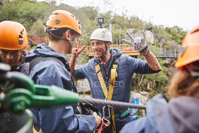 Enthusiastic man preparing to zip line, gesturing peace sign — Stock Photo