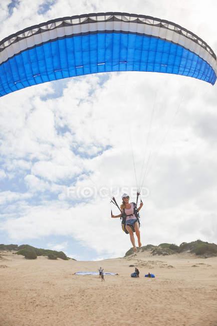 Feminino parapente com para-quedas decolando na praia — Fotografia de Stock