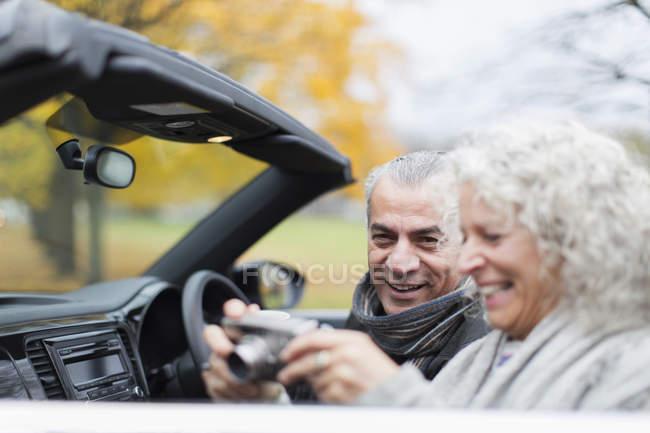 Seniorenpaar benutzt Digitalkamera im Cabrio — Stockfoto