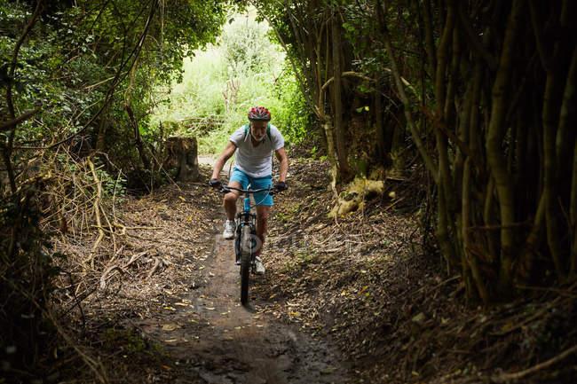 Зрелый человек катается на горном велосипеде по лесам — стоковое фото