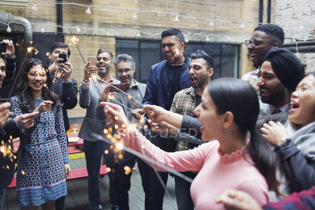 Friends enjoying party, celebrating with sparklers — Stock Photo