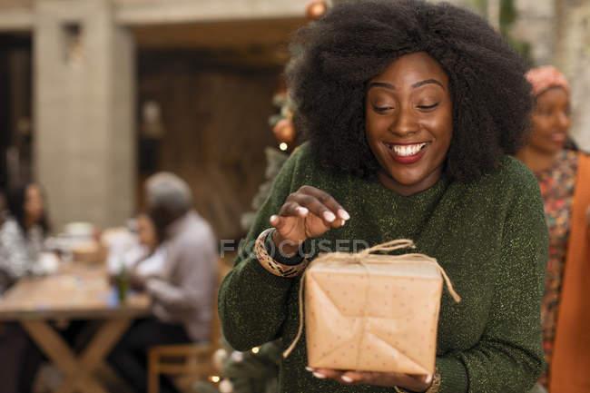 Mujer joven curiosa, entusiasta abriendo regalo de Navidad - foto de stock