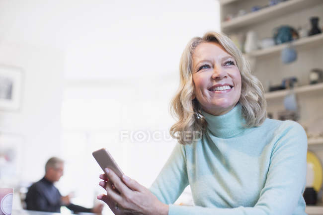 Smiling, confident mature woman using smart phone — Stock Photo
