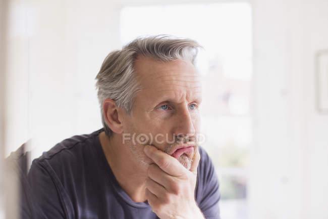Homme mûr, touchant le visage dans le miroir de salle de bain — Photo de stock