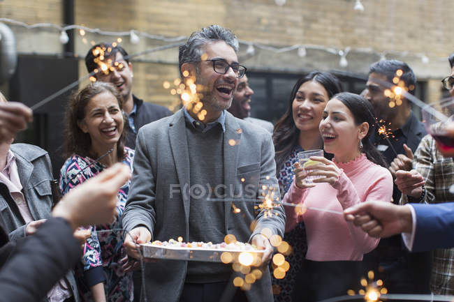 Friends celebrating birthday with cake and sparklers — Stock Photo