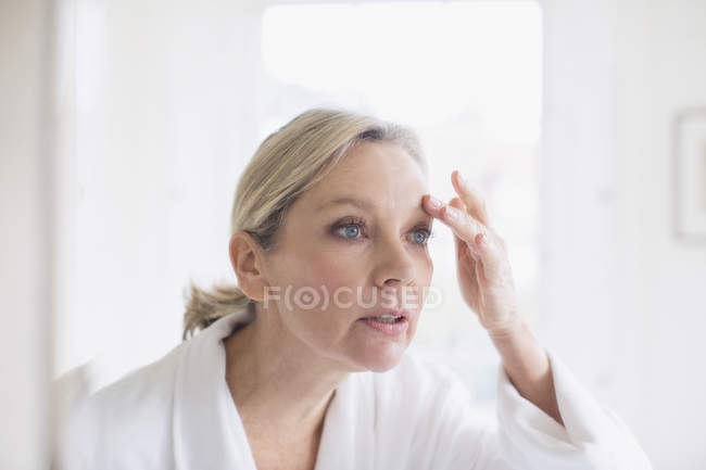 Mature woman touching eyebrow at bathroom mirror — Stock Photo