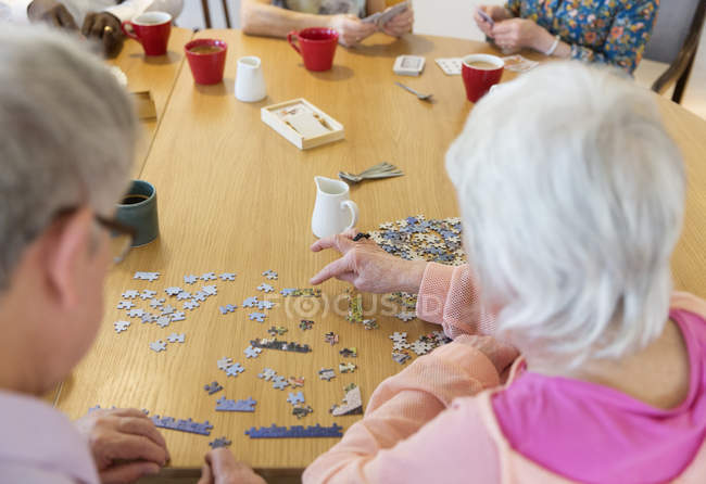 Senior friends assembling jigsaw puzzle at table in community center — Stock Photo