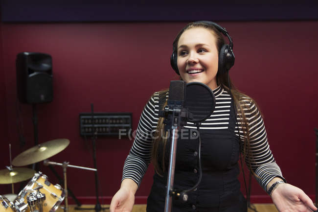 Confident teenage girl recording music, singing in sound booth — Stock Photo