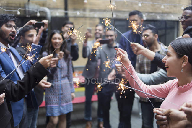 Friends celebrating with sparklers at party — Stock Photo