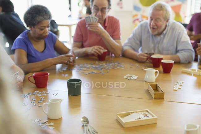 Amigos mayores jugando juegos en la mesa en el centro comunitario - foto de stock