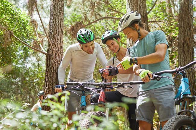 Friends mountain biking, using wearable camera in woods — Stock Photo