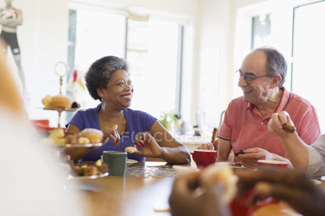 Happy senior friends enjoying afternoon tea in community center — Stock Photo
