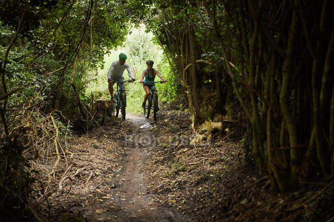 Couple mountain biking on trail in woods — Stock Photo