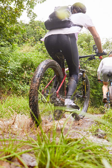 Woman mountain biking on muddy trail — Stock Photo