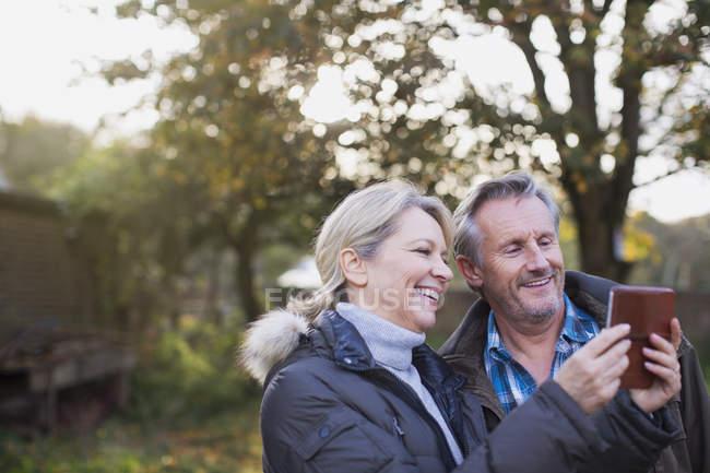 Зрелые Кавказский пара принимая фото на смартфоне на Осенний парк — стоковое фото