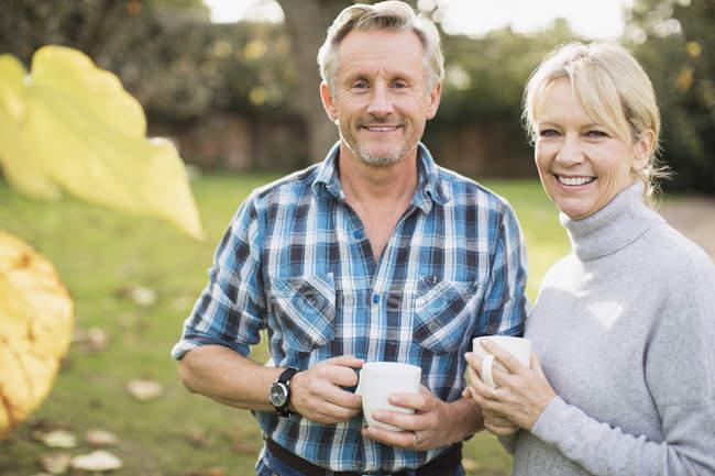 Pareja caucásica tomando café en el jardín - foto de stock