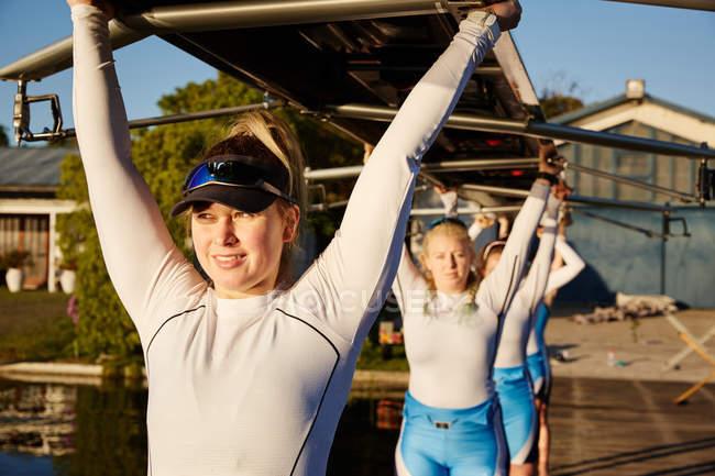 Zuversichtlich, entschlossene Frau Rudern Team heben Scull overhead auf sonnigen dock — Stockfoto