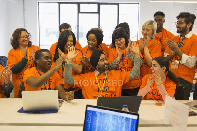 Enthusiastic hackers celebrating, coding for charity at hackathon — Stock Photo
