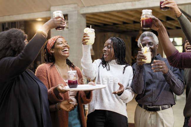 Enthusiastic multi-generation family toasting lemonade and sangria on patio — Stock Photo