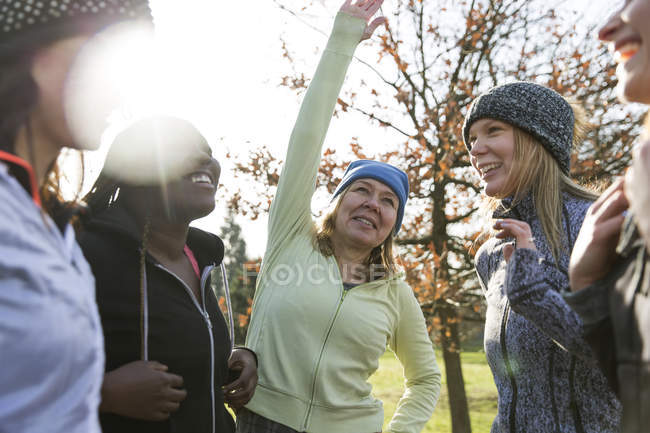 Female runners stretching and talking in sunny park — Stock Photo