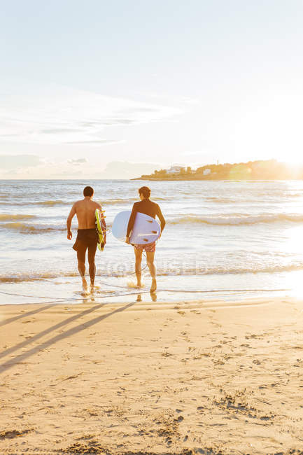 Male surfers carrying surfboards into ocean on sunny beach — Stock Photo