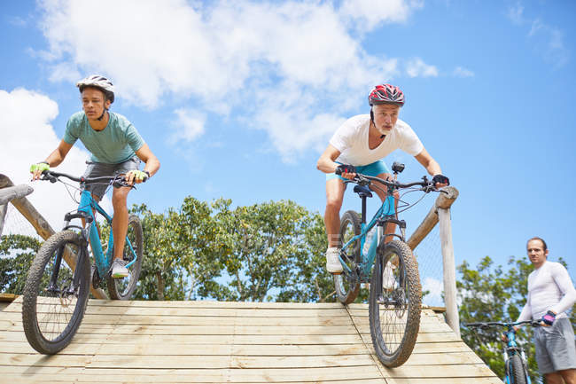 Focused men mountain biking on obstacle course ramp — Stock Photo