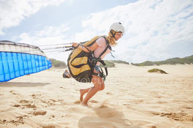 Feminino parapente executando com para-quedas na praia ensolarada — Fotografia de Stock