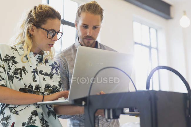 Designers with laptop at 3D printer in office — Stock Photo