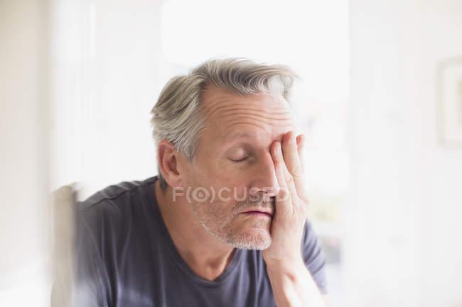 Набридло зріла людина з головою в руках в дзеркало — стокове фото