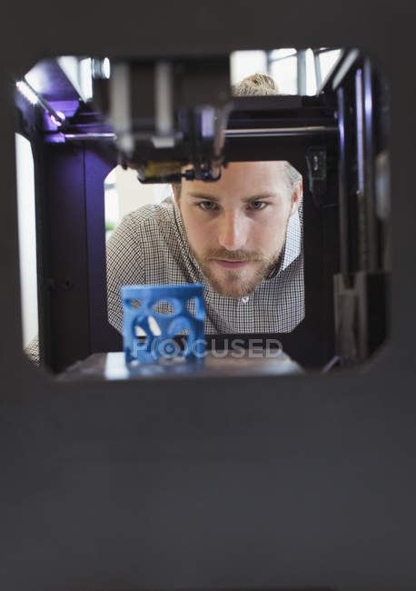 Concepteur masculin concentré regardant l'imprimante 3D — Photo de stock