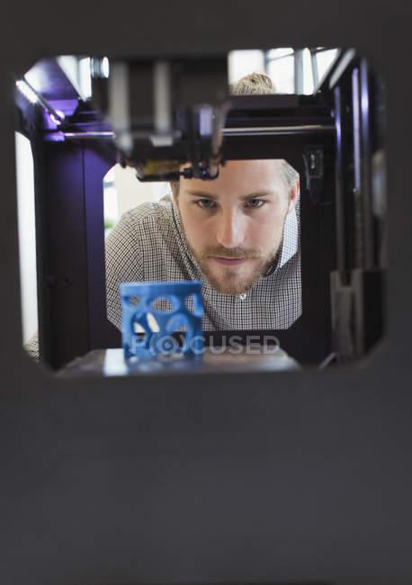 Diseñador masculino enfocado viendo impresora 3D - foto de stock