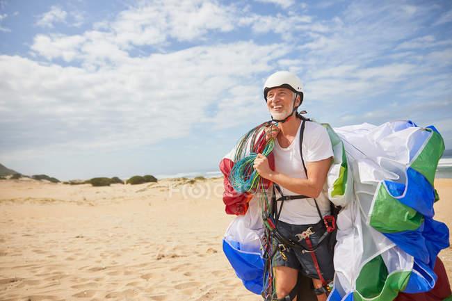 Sorridente parapendio maschile che trasporta attrezzatura e paracadute sulla spiaggia soleggiata — Foto stock