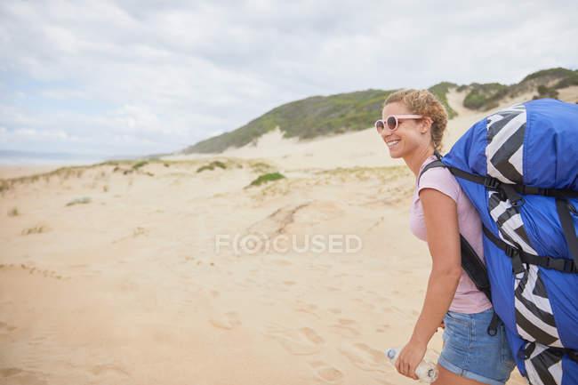 Parapendio femminile sorridente con zaino paracadute sulla spiaggia — Foto stock