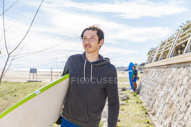 Male surfer carrying surfboard on sunny beach — Stock Photo