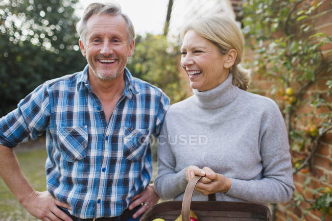 Mature caucasian couple standing with fruit basket at garden — Stock Photo