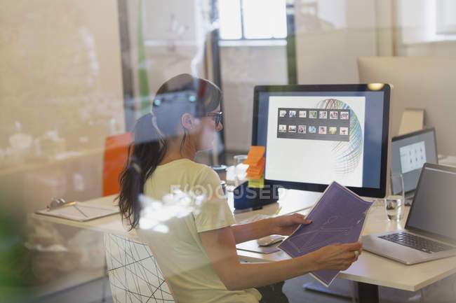 Female designer working at computer in office — Stock Photo