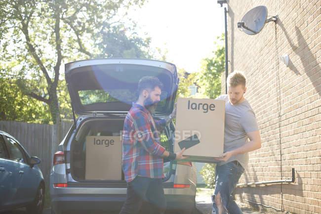 Мужчина гей пара разгружает движущиеся коробки из машины — стоковое фото