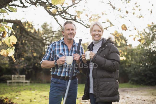 Mature caucasien couple avec des râteaux, boire du café au jardin — Photo de stock
