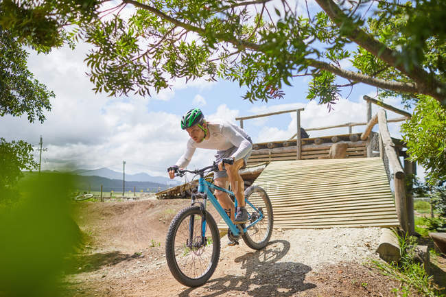 Focused man mountain biking down sunny obstacle course ramp — Stock Photo
