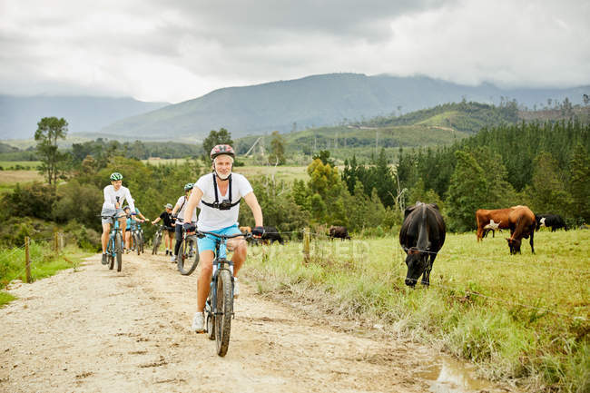 Man mountain biking with friends on rural dirt road along cow pasture — Stock Photo