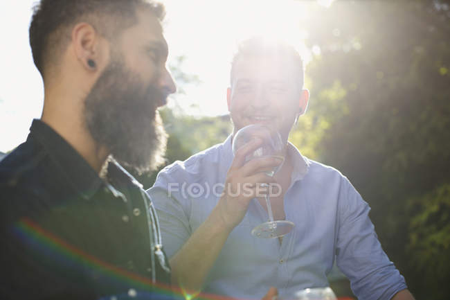 Male gay couple drinking wine and talking — Stock Photo