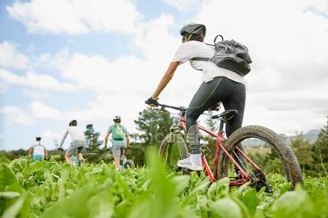Друзья катаются на горных велосипедах в сельской местности — стоковое фото