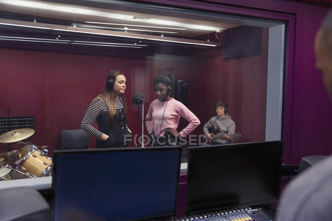 Teenage musicians recording music, singing in sound booth — Stock Photo