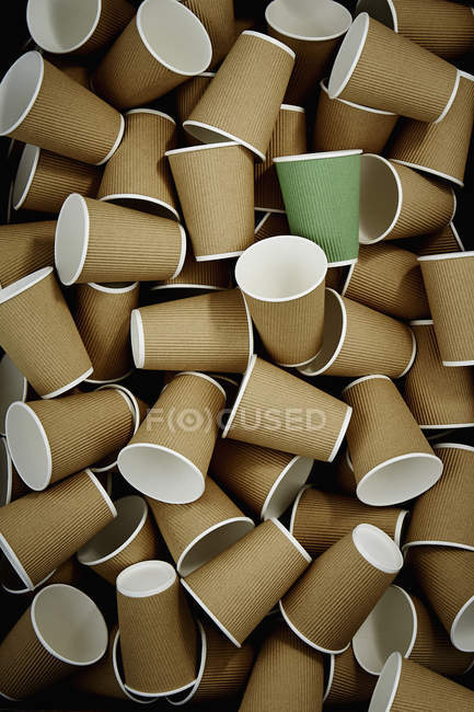 Full frame green recyclable coffee cup among disposable cups — стоковое фото