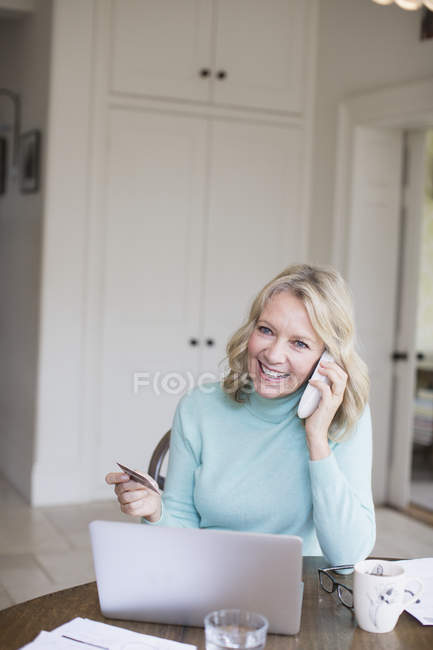 Smiling mature woman with credit card talking on telephone at laptop — Stockfoto