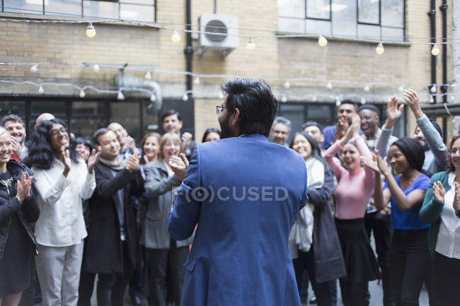 Business people cheering for businessman in courtyard — Stock Photo