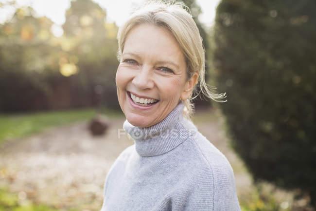 Ritratto di felice donna bionda in maglione grigio in giardino — Foto stock