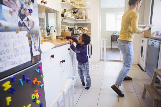 Afro-americano filho ajudando a mãe na cozinha — Fotografia de Stock