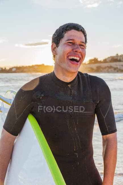 Laughing male surfer with surfboard on beach — Stock Photo